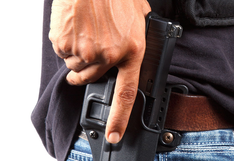 hand on gun in holster